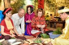 Amigos extranjeros disfrutan la elaboración del pastel típico del Tet