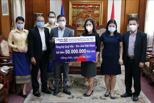 Vietnamitas en Laos contribuyen al fondo nacional de vacunas contra el COVID-19 hinh anh 1